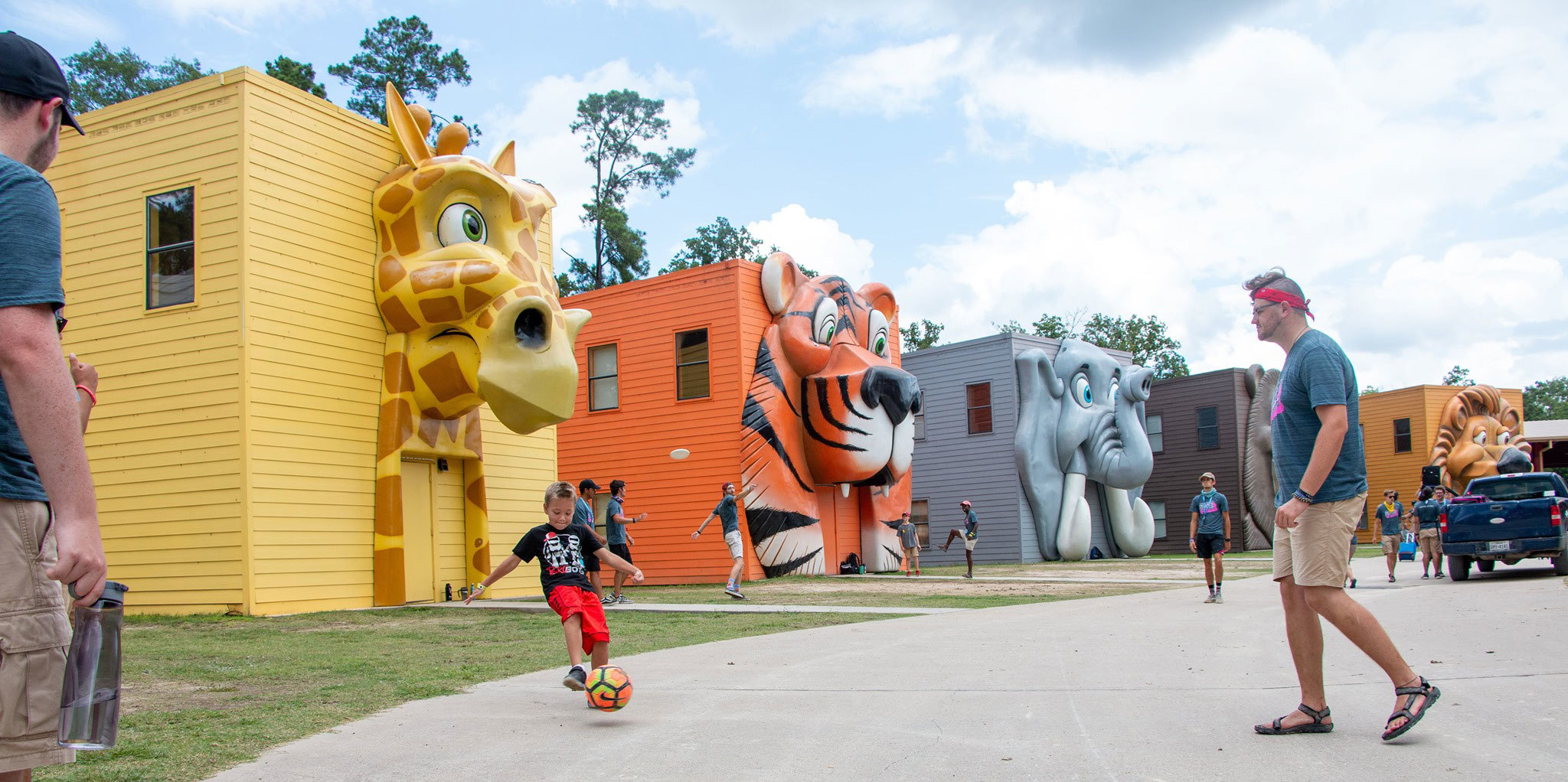 Kids and Parents Playing Outside Giant Animal Face Fascade Camp Cabins at Carolina Creek Christian Camp