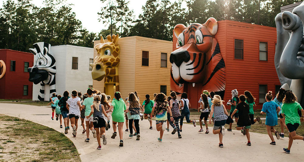 Group of Teen Girls Running in Front of Giant Animal Building Fascades on Camp Cabins